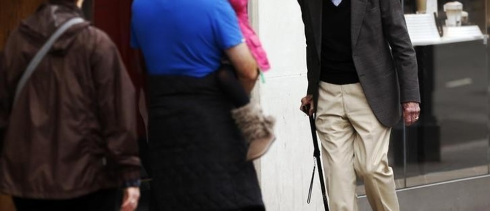"""A man walking with the help of a cane passes a family on a street in London October 18, 2013. Britain's Health Secretary Jeremy Hunt said in a speech at the National Children and Adults Services (NCAS) conference on Friday that it is a national shame that """"there are 800,000 people in England who are chronically lonely"""", quoting the Campaign to End Loneliness for the figure, according to local media.  REUTERS/Luke MacGregor  (BRITAIN - Tags: SOCIETY HEALTH)"""