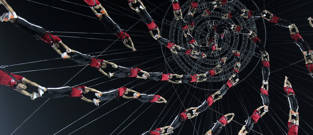 Students of Shaolin Tagou Martial Arts School are suspended in mid-air as they practise in a dress rehearsal for a stunt performance which is part of the opening ceremony of the 2014 Nanjing Youth Olympic Games, at a stadium in Nanjing, Jiangsu province August 14, 2014.