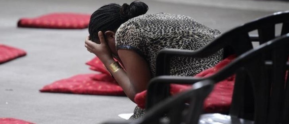 A woman holds her head after looking at the blast remains inside the Assumption Church in Kathmandu May 23, 2009. Two people were killed and at least a dozen wounded when an explosion ripped through a church near the Nepali capital on Saturday, police said, hours before the country's parliament was set to elect a new prime minister. REUTERS/Shruti Shrestha (NEPAL DISASTER RELIGION)