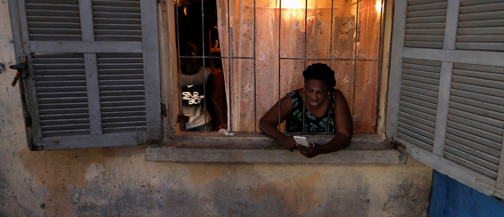A woman uses her mobile phone as she stands at her home window before a curfew, amid the spread of the coronavirus disease (COVID-19) in Pikine suburb of Dakar, Senegal April 22, 2020