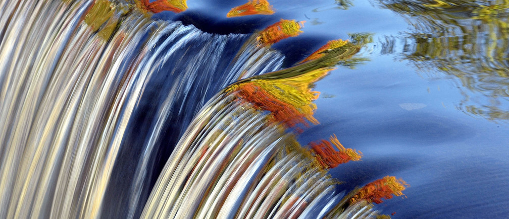 The colors of Fall can be seen reflected in a waterfall along the Blackberry River in Canaan, Connecticut October 13, 2004. NO RIGHTS CLEARANCES OR PERMISSIONS ARE REQUIRED FOR THIS IMAGE. REUTERS/Jessica Rinaldi Pictures of the Month October 2004 Pictures of the Year 2004  JRAlso see GF2DWDIWLOAA - RP5DRICUDBAA