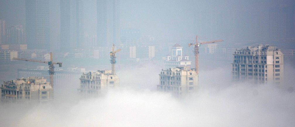 Buildings under construction are seen during a hazy day in Rizhao, Shandong Province, China, March 15, 2016.