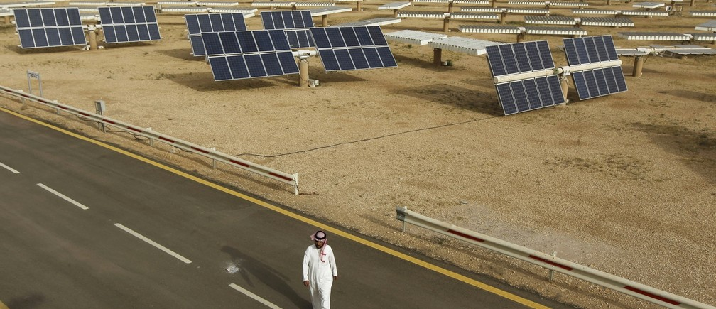 A Saudi man walks on a street past a field of solar panels at the King Abdulaziz city of Sciences and Technology, Al-Oyeynah Research Station May 21, 2012.