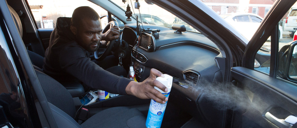 "Uber and Lyft driver Adama Fofana, who says he and other drivers he knows have ""fear in their stomachs"" about contracting the coronavirus disease (COVID-19) while working, but cannot cut their hours because they need the income to survive, sprays disinfectant in his car in New York City, New York, U.S., March 9, 2020. Picture taken March 9, 2020. REUTERS/Joe Penney - RC2QLF94E5T2"