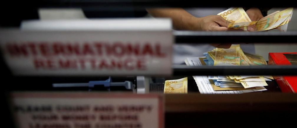 A teller counts Philippine peso bills at an international money remittance center in Makati City, Metro Manila, Philippines September 19, 2018