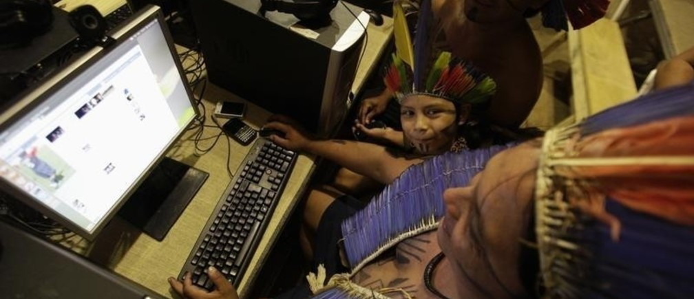 Indigenous people from the Terena tribe use Facebook at Kari-Oca village in Rio de Janeiro