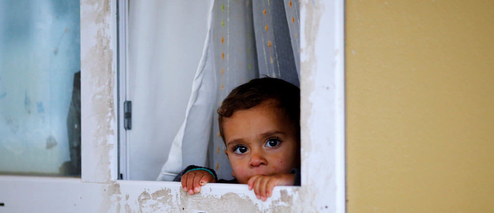 A Syrian refugee child looks out from their container in Elbeyli refugee camp near the Turkish-Syrian border in Kilis province, Turkey, December 1, 2016. REUTERS/Umit Bektas - RTSU6JL