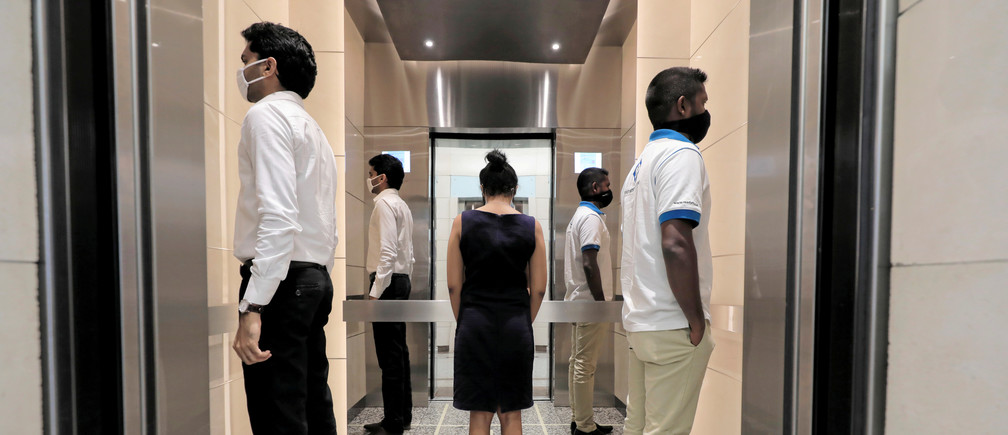 People practice social distancing inside an elevator prior to arriving to their work places at World Trade Center, after the government announced that private and state companies will reopen their offices after almost two months of lockdown amidst concerns about the spread of coronavirus disease (COVID-19) in Colombo, Sri Lanka May 11, 2020.