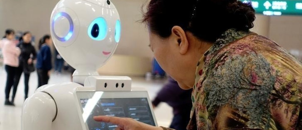 A woman touches a screen on a robot developed by iFlytek at the outpatient hall of People's Liberation Army General Hospital in Beijing, China March 16, 2017. Picture taken March 16, 2017.  Zhao Naiming/via REUTERS