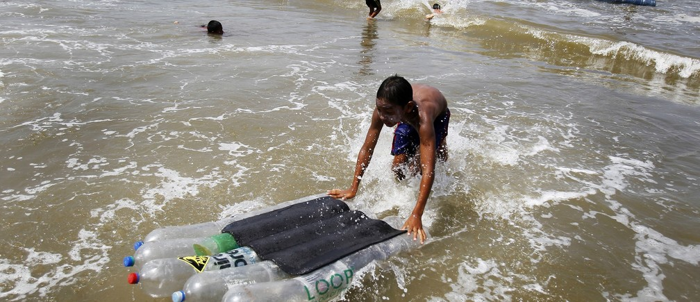 A boy pushes a board made with plastic bottles during a surfing lesson at a beach in Lima, February 27, 2014.