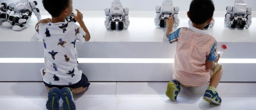 Children play with robots at the 2017 World Robot Conference in Beijing, China August 22, 2017.   REUTERS/Thomas Peter