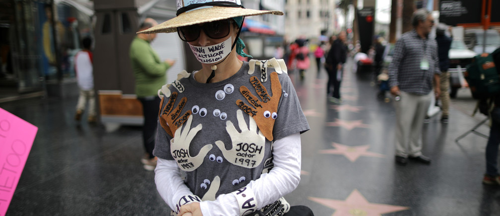 A woman wears an outfit with the names of all the men in Hollywood who sexually harassed her, during a #MeToo protest march in LA, November 2017.