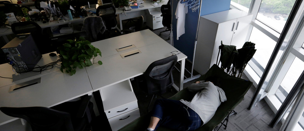 "Kou Meng, product manager of RenRen Credit Management Co., sleeps on a camp bed at the office early morning, in Beijing, China, April 27, 2016. Office workers sleeping on the job is a common sight in China, where a surplus of cheap labour can lead to downtime at work. But in China's technology sector, where business is growing faster than many start-up firms can hire new staff, workers burn the midnight oil to meet deadlines and compete with their rivals. Some companies provide sleeping areas and beds for workers to rest during late nights. REUTERS/Jason Lee       SEARCH ""JASON SLEEP"" FOR THIS STORY. SEARCH ""THE WIDER IMAGE"" FOR ALL STORIES   - S1BETDIDDXAA"