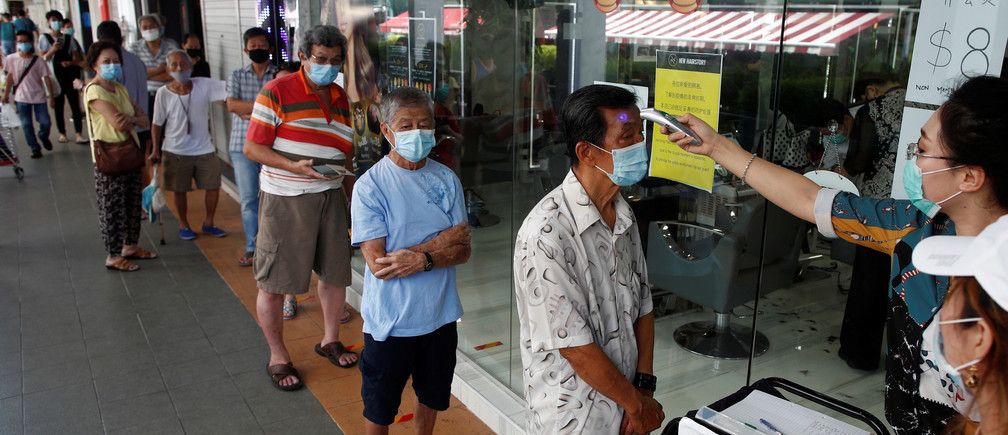 Customers queue up to have their temperature taken outside a hairdressing salon as they reopen for business amid the coronavirus disease (COVID-19) outbreak in Singapore May 12, 2020. REUTERS/Edgar Su - RC2QMG9SJI9R