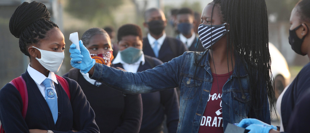 A teacher screens students as schools begin to reopen after the coronavirus disease (COVID-19) lockdown in Langa township in Cape Town, South Africa June 8, 2020. REUTERS/Mike Hutchings - RC2X4H9294C4