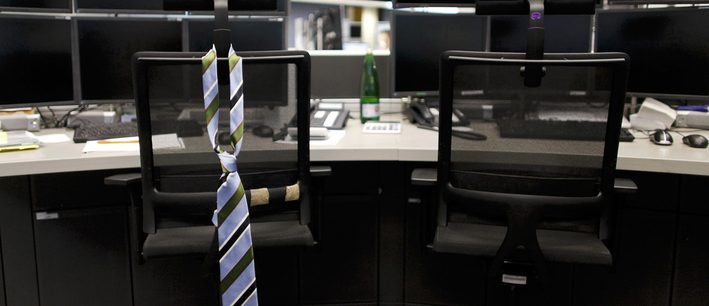 A tie hangs from an empty chair on a trader desk after the end of a trading day at the Frankfurt stock exchange August 12, 2011. REUTERS/Alex Domanski (GERMANY - Tags: BUSINESS IMAGES OF THE DAY) - GM1E78D02RY01