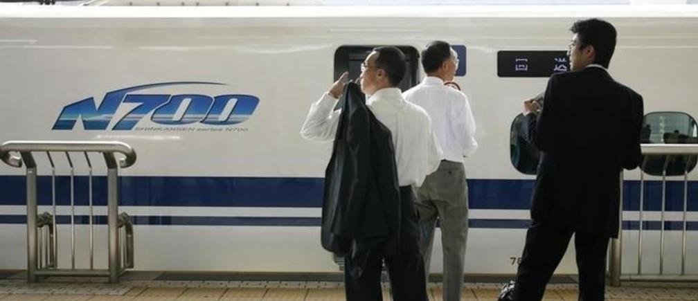 Businessmen stand in front of Japan Railway's new N700 bullet train at a platform of Tokyo Station in Tokyo July 6, 2007.  REUTERS/Toru Hanai (JAPAN)