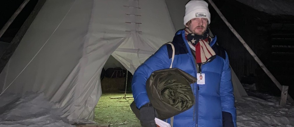 Clutching his Swiss army issue sleeping bag, Andrew Funk stands in front of the teepee he's called home for Davos
