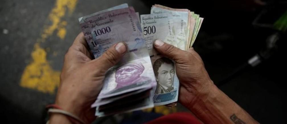 A worker counts Venezuelan bolivar notes at a gas station of Venezuelan state oil company PDVSA in Caracas, Venezuela December 1, 2017. REUTERS/Marco Bello