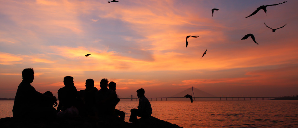 A group of men are silhouetted as they sit on a sea wall along the Arabian Sea in Mumbai at sunset October 24, 2013.