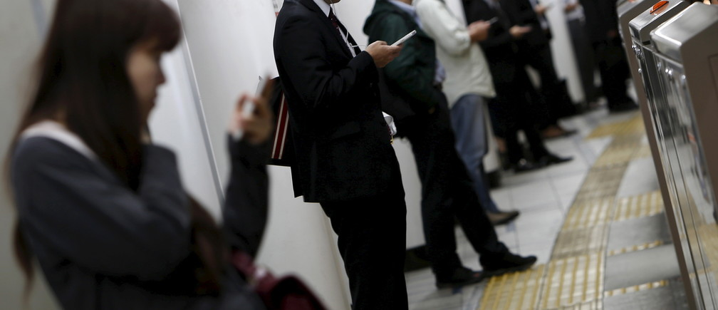 People look at their mobile phones while waiting for a train at a subway station in Tokyo, Japan, October 14, 2015.  Japanese manufacturers' confidence worsened for the second straight month and is expected to fade going forward, a Reuters poll showed, adding to lingering fears of a recession and keeping policymakers under pressure to deploy fresh stimulus. Picture taken October 14, 2015. REUTERS/Yuya Shino - GF10000244901