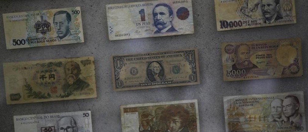 U.S. dollar (C) and several foreign currencies are pictured at a currency exchange office in Rio de Janeiro, Brazil, August 31, 2015.