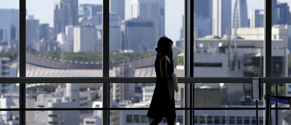 A woman uses her mobile phone at an office building in Tokyo July 21, 2015. Two in five Japanese firms plan to boost capital spending this business year, and more than a third of those say it is because of rising demand, a Reuters poll showed, pointing to a pickup in confidence about the economy. Picture taken July 21, 2015. REUTERS/Toru Hanai  - GF10000165729