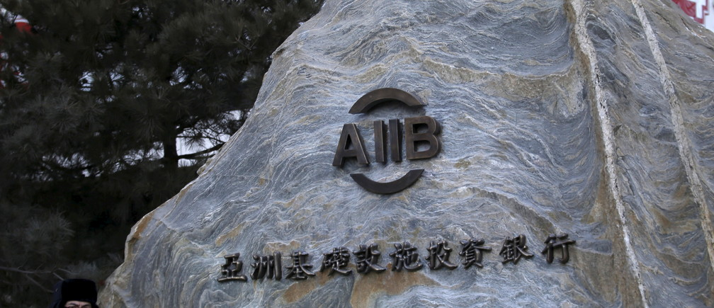 A security guard stands in front of the signboard of Asian Infrastructure Investment Bank (AIIB) at its headquarter building in Beijing January 17, 2016.