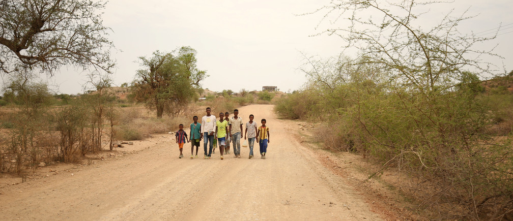 Students walk home from school in the outskirts of Badme, territorial dispute town between Eritrea and Ethiopia currently occupied by Ethiopia, June 8, 2018. Picture taken June 8, 2018. REUTERS/Tiksa Negeri - RC1445342050
