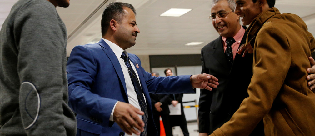 Aquel Aziz (2nd L) is reunited with his sons Tareq Aziz (L) and Ammar Aziz (R), Yemeni nationals who were initially denied entry into the U.S. because of the recent travel ban, at Washington Dulles International Airport in Chantilly, Virginia, U.S. February 6, 2017.  REUTERS/Jonathan Ernst - RTX2ZVVQ