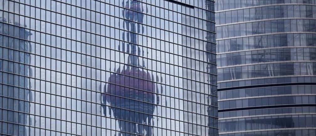 The Oriental Pearl TV Tower reflected on the facade of another building at Pudong financial district in Shanghai April 2, 2014. China's Vice Premier Zhang Gaoli called for faster construction of certain important projects on Tuesday, in remarks that may feed speculation that China will increase state spending in coming months to bolster its stuttering economy. China's economy has had a surprisingly soft start to the year, rattling investors who had expected a stable performance and who now fear China may drag on global growth. Two surveys on Tuesday showed China's manufacturing sector remained weak in March. REUTERS/Carlos Barria  (CHINA - Tags: BUSINESS CITYSCAPE MEDIA TPX IMAGES OF THE DAY) - GM1EA421F8L01