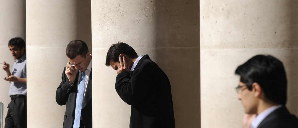 City workers make phone calls outside the London Stock Exchange in Paternoster Square in the City of London at lunchtime October 1, 2008. European policymakers have called on the U.S. Senate to approve a revised rescue plan aimed at tackling the worst financial crisis since the 1930s. REUTERS/Toby Melville (BRITAIN) - GM1E4A11PQ101