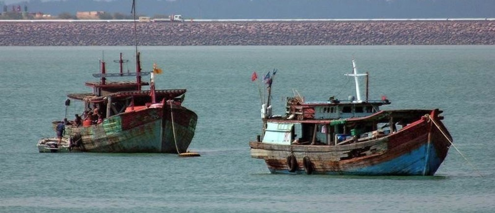 A man boards an impounded illegal fishing vessel moored at the northern city of Darwin in this picture taken May 11, 2005. Australia has spent tens of millions of dollars boosting its border security to deal with Indonesian fishermen venturing into Australian waters to fish for lucrative shark fin because they have depleted their own stocks. Picture taken May 11, 2005. To match feature Australia-Fishing REUTERS/David Gray - RP2DSFHPKVAA