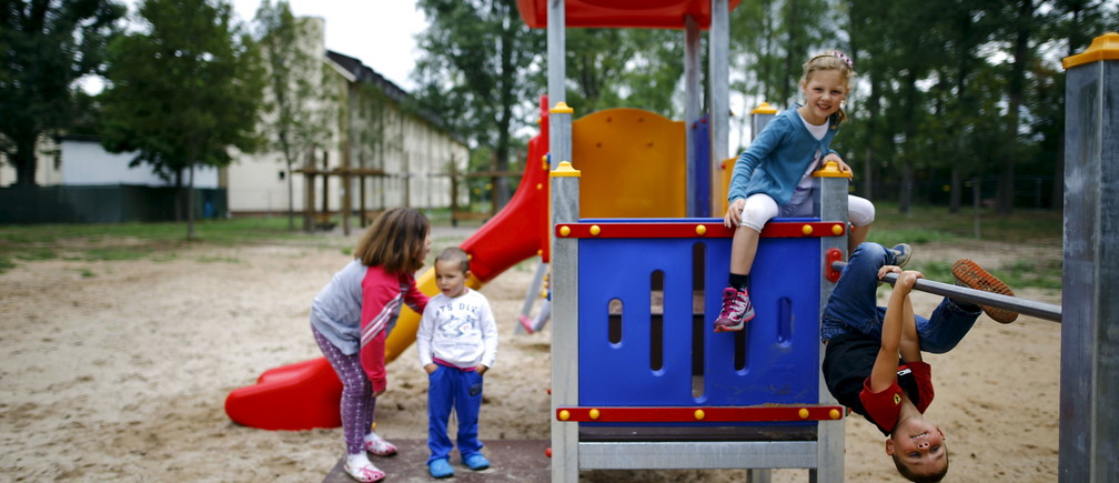 """Four-year old Tom (R) and his six-year old sister Lisa from Offenbach show Serbian refugee Dragan (2nd L) and his sister Tamara (L) how to play on the climbing frame at a refugee camp in Hanau, Germany, August 18, 2015. Tom and Lisa learned from her mother that a lot of refugees come to Germany and most of them, especially the children, don't have much clothes or toys to play with. The two German youngsters than decided to visit the refugee camp to donate from their own wardrobe and toys and """"make friends"""" with the kids from abroad.   REUTERS/Kai Pfaffenbach  - RTX1ONYJ"""