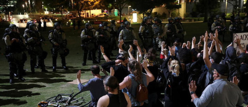 Demonstrators raise their hands as they wait for LASD officers to detain them during a protest in response to the death in Minneapolis police custody of George Floyd, in Los Angeles, California, U.S., June 3, 2020. Picture taken June 3, 2020. REUTERS/Patrick T. Fallon
