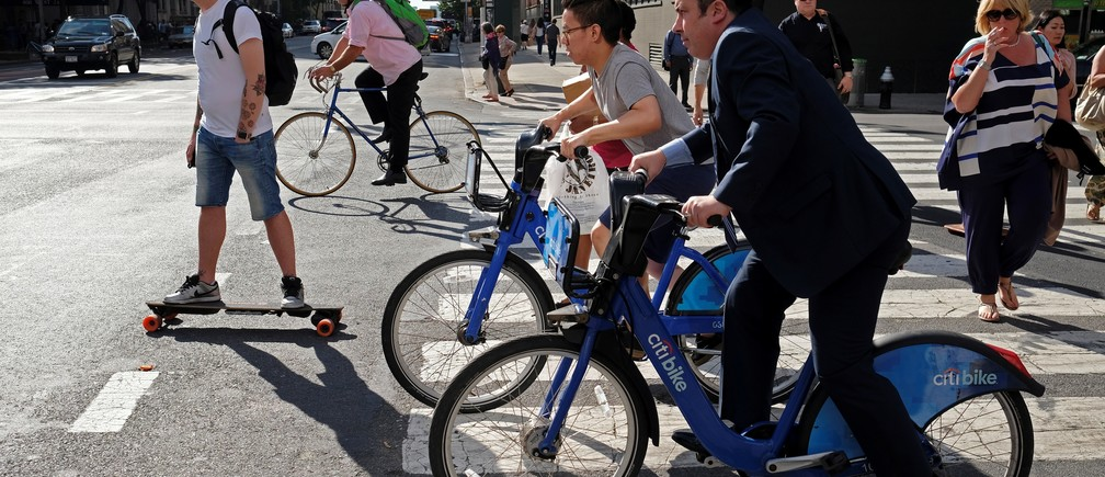 Clients of bicycle sharing service Citi Bike and others wait for a traffic light to turn green along Ninth Avenue in Manhattan, New York, U.S., June 15, 2016. REUTERS/Rickey Rogers - RTX2GHDN