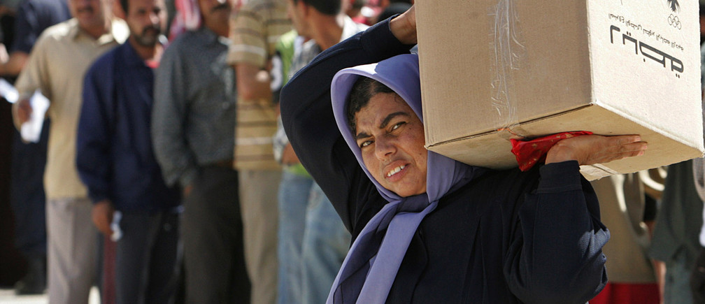 """A woman carries a parcel of food donated by a Jordanian charity, """"Tikyet Um Ali"""", in the northern Jordanian city of Irbid October 15, 2006. Moslem charities alongside government sponsored funds compete to get donations during Ramadan from wealthy Muslims seeking God's mercy by giving part of their income to the poor. To match feature JORDAN-ZAKAT  Picture taken October 15, 2006.  REUTERS/Muhammad Hamed     (JORDAN) - GF1DTTTILJAA"""