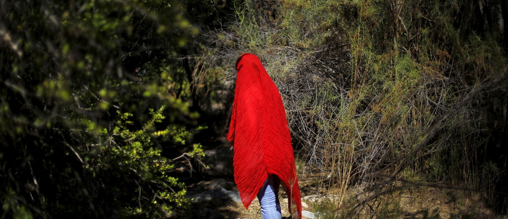 A human rights activist walks through a native forest at the Pupio estuary in the middle of the road between a waste deposit tank of Los Pelambres mine and Caimanes town at the El Mauro valley, April 1, 2015.