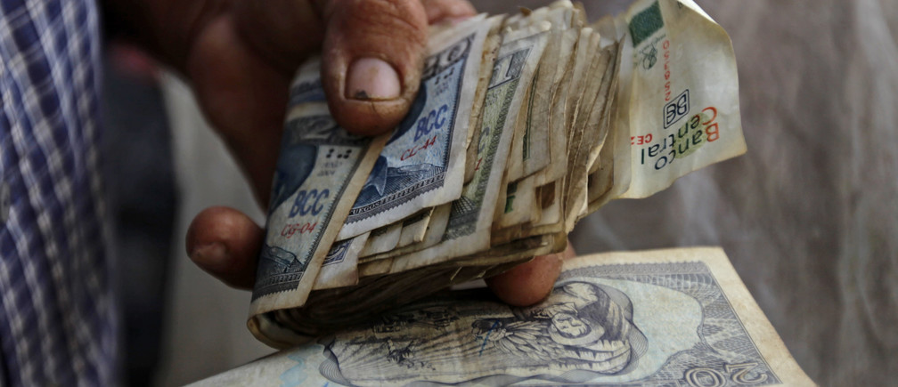 A farmer holds a wad of Cuban money at a vegetable stall at a market in Sagua La Grande, in the province of Villaclara in central Cuba, around 240 km (149 miles) east of Havana October 12, 2013. Cuba took the first step towards scrapping its two-tier currency on October 22, 2013, in a move which could boost local workers' income and remove a major hurdle for importers and exporters. Cuba's convertible peso (CUC) is pegged to the U.S. dollar, while the local peso (CUP) is valued at a fraction of the greenback's value, angering the population which is paid in the latter, and complicating accounting, the evaluation of performance, and trade for state companies. Picture taken October 12, 2013. REUTERS/Desmond Boylan (CUBA - Tags: SOCIETY BUSINESS AGRICULTURE)