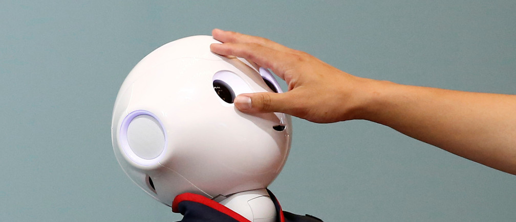 A man touches the head of a SoftBank humanoid robot known as Pepper at the venue for Pepper World 2016 Summer, ahead of its opening on Thursday, in Tokyo, Japan, July 20, 2016.