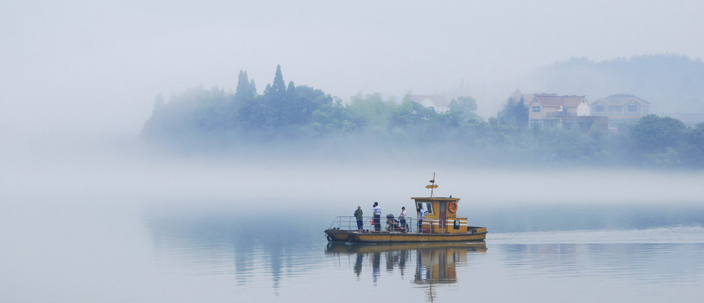 A ferry travels through thick fog over Xin'an River in Jiande, Zhejiang province June 12, 2013.