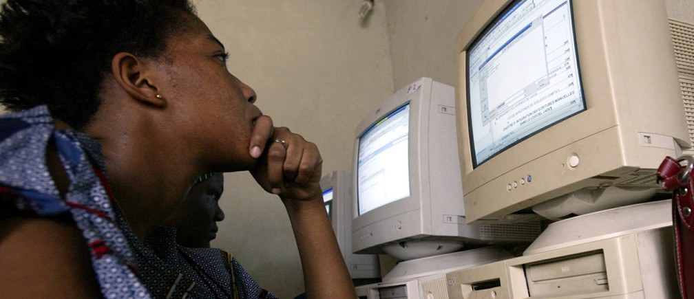 A girl looks the screen of a computer as she works in a cybercafe in Abidjan on November 18, 2005. - RTXNZOA