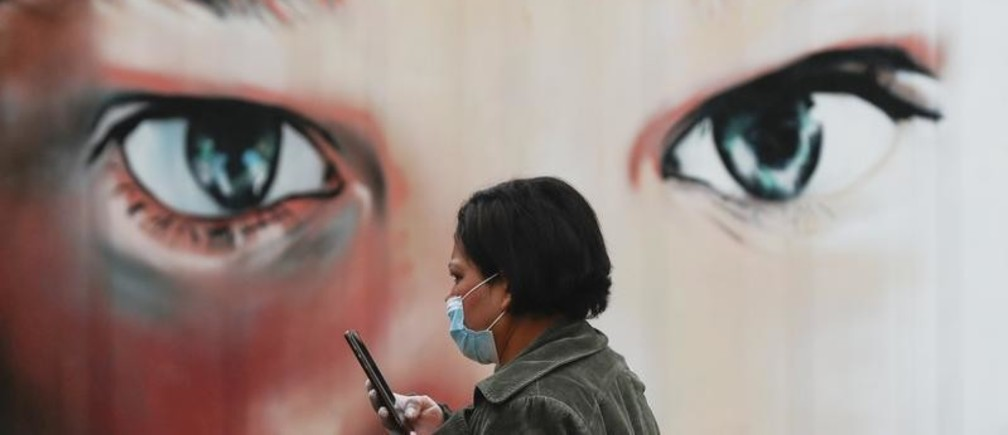 A woman wearing a protective mask and gloves walks outside a hospital during the partial lockdown as part of a 15-day state of emergency following the coronavirus disease outbreak in Madrid, Spain March 17, 2020. REUTERS/Susana Vera - RC2NLF97NATC