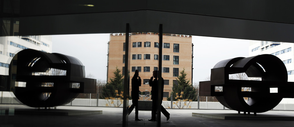 A man walks past the logo of Spanish oil major Repsol at its headquarters in Madrid February 26, 2015. Spanish oil group Repsol said its 2014 adjusted clean net profit jumped 27.1 percent, boosted by a big boost in refining margins that more than offset falling revenue in its production business amid plummeting world oil prices. REUTERS/Susana Vera (SPAIN - Tags: BUSINESS ENERGY LOGO) - RTR4R8YF