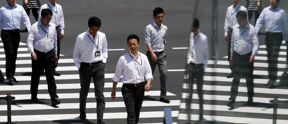 Office workers are reflected in a glass railing as they cross a street during lunch hour in Tokyo June 1, 2015. REUTERS/Thomas Peter