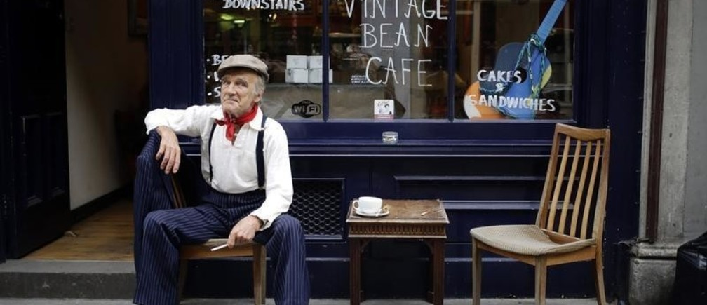 Mick, a genuine east end Cockney, sits with a cup of tea and a cigarette at a cafe near Brick Lane in London September 22, 2013. Mick supplements his state pension by dressing up and allowing himself to be photographed for a pound amongst the streets around Brick Lane that are lined with vintage shops.      REUTERS/Kevin Coombs   (BRITAIN - Tags: TRAVEL SOCIETY TPX IMAGES OF THE DAY) - GM1E99N08A001