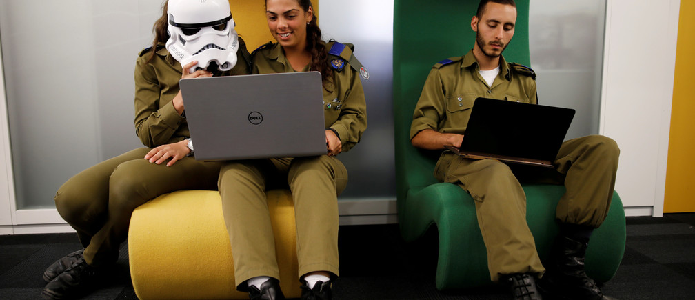 Israeli soldiers, one wearing a Star Wars Storm Trooper Voice Changing Helmet, work on laptops as they take part in a cyber security training course, called a Hackathon, at iNT Institute of Technology and Innovation, at a high-tech park in Beersheba, southern Israel August 28, 2017. Picture taken August 28, 2017. REUTERS/Amir Cohen     TPX IMAGES OF THE DAY - RC17FB526740