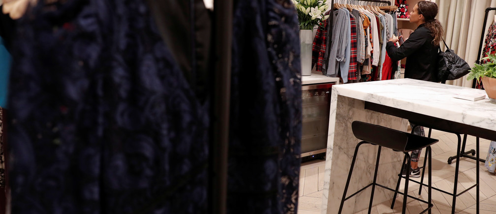 A woman looks at clothes at the Rent The Runway store, an online subscription service for women to rent designer dress and accessory items, in New York City, New York, U.S., September 12, 2019. Picture taken September 12, 2019. REUTERS/Shannon Stapleton - RC16BAFFCC50