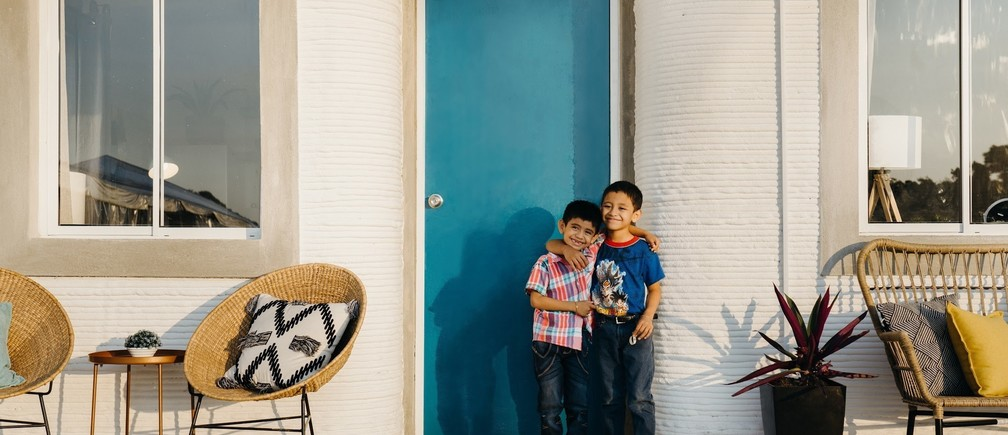 children in front of a 3D-printed home in Mexico