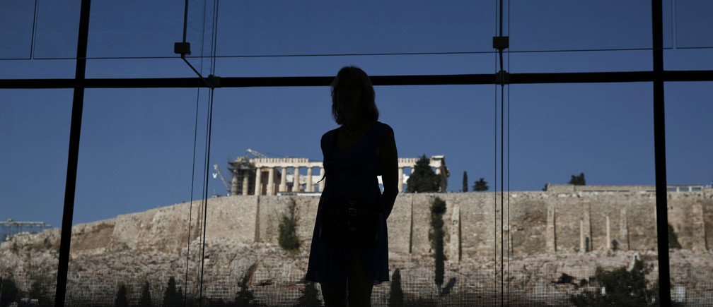 A woman looks at exhibits on display in the Parthenon hall at the Acropolis museum, as the temple of the Parthenon is seen in the background, in Athens October 10, 2014. Human rights lawyer Amal Alamuddin Clooney, fresh from her marriage to Hollywood heart-throb George Clooney last month, is heading to Athens to advise the Greek government in its battle to repatriate the ancient Elgin Marbles statues from Britain. The Marbles are a set of ancient Greek sculptures taken to London after being removed from the Acropolis in Athens by a British aristocrat, Lord Elgin, while Athens was under Ottoman control in the 19th Century. Greece has sought their return from the British Museum for decades, to no avail.    REUTERS/Yorgos Karahalis (GREECE - Tags: POLITICS SOCIETY TRAVEL ENTERTAINMENT) - RTR49O0A